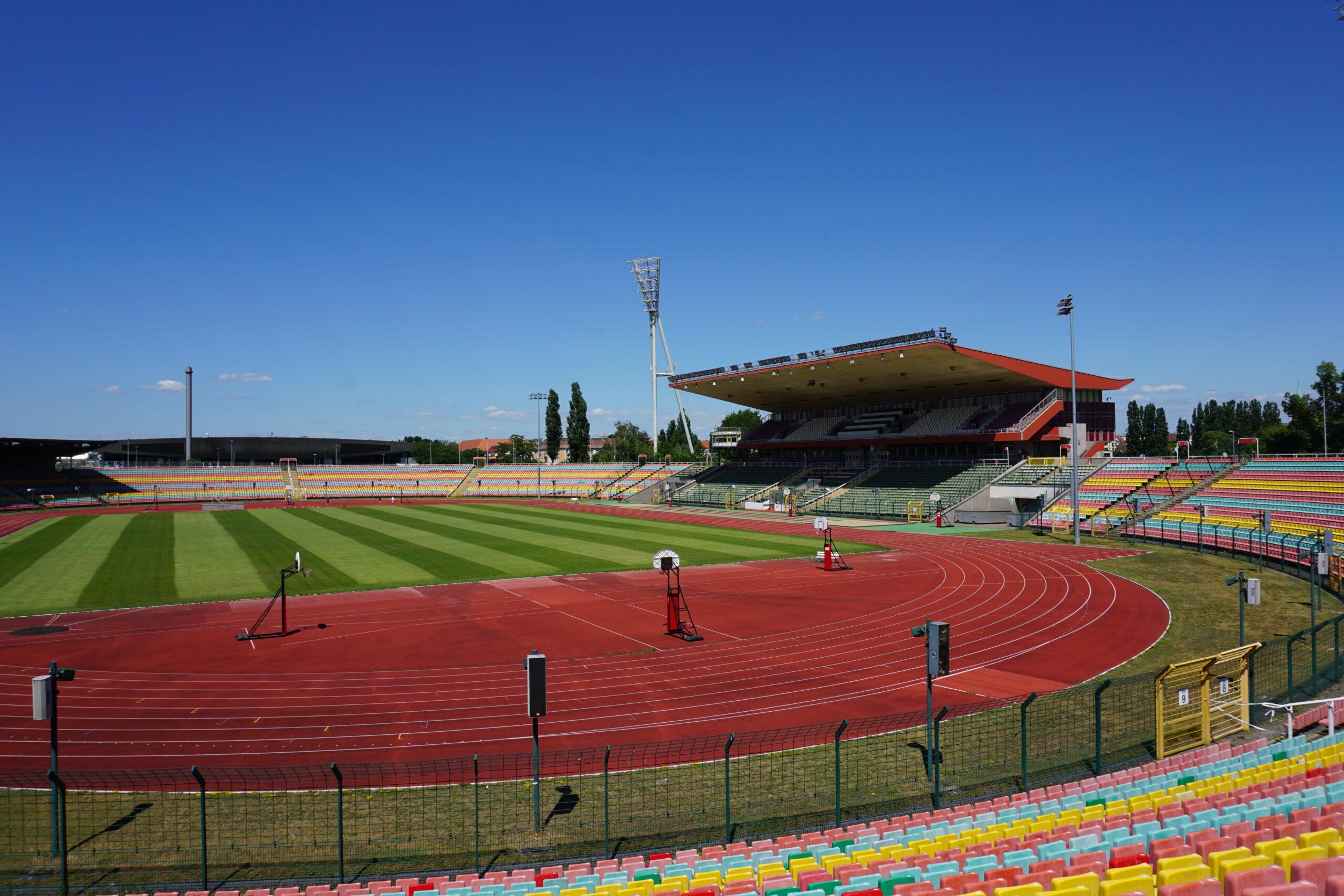 Foto zeigt die Innenansicht des Stadions im Jahnsportpark Berlin. Es ist ein Lauffeld, der großer Rasen und die Tribüne abgebildet.