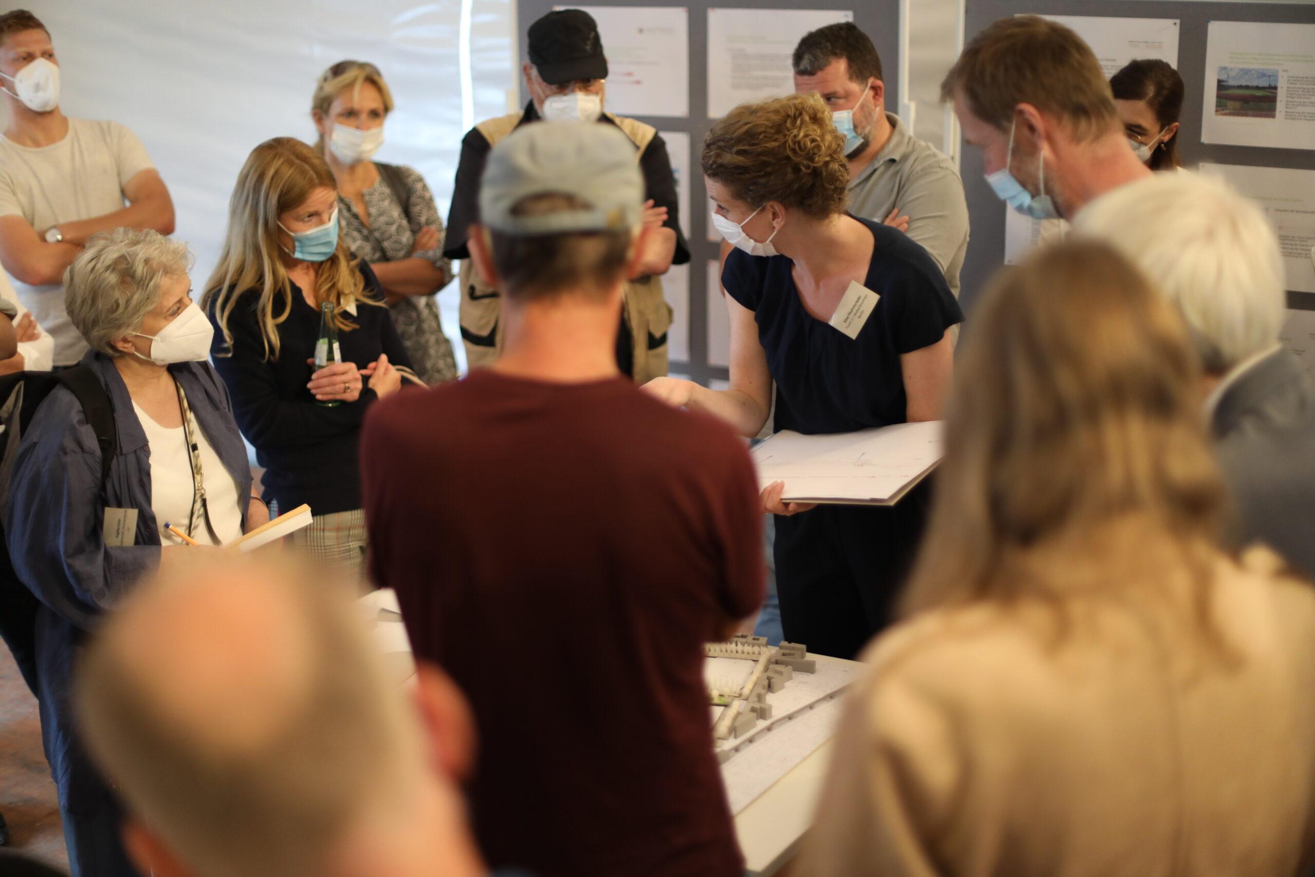 Teilnehmende stehen im Workshopzelt um einen Tisch und diskutieren